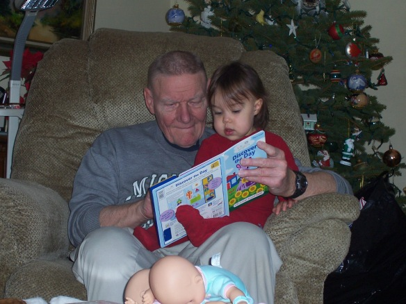 A photo of Carl Diener reading a book to Ava Diener.
